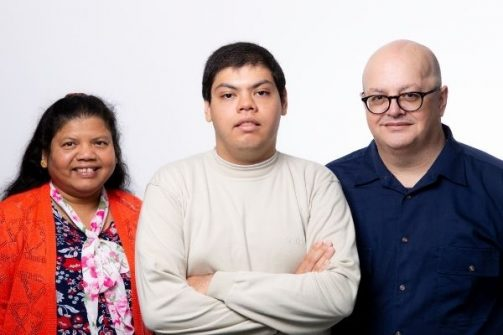 Autistic man standing in the middle of his two parents